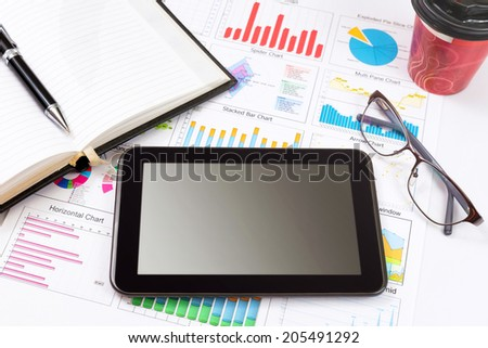 Business detail of a tablet lying on top of business charts and graphs. - stock photo