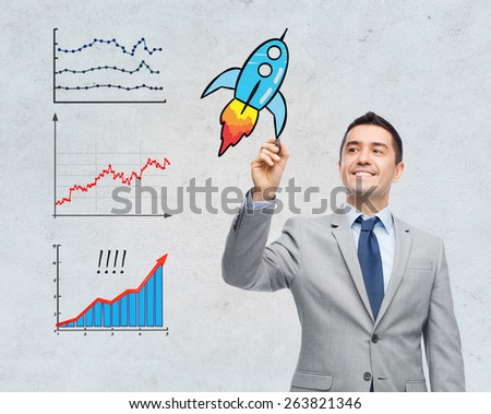 business, development, management and people concept - happy smiling businessman in suit writing or drawing something imaginary with marker over gray background - stock photo