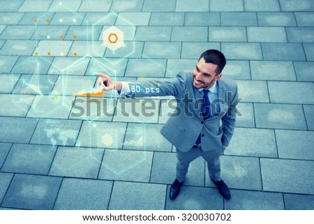 business, development, technology and people concept - young smiling businessman pointing finger to virtual screens with chart projection outdoors from top - stock photo