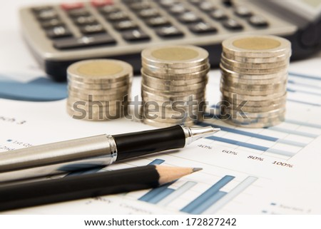 Business diagram on financial report with coins and calculator - stock photo