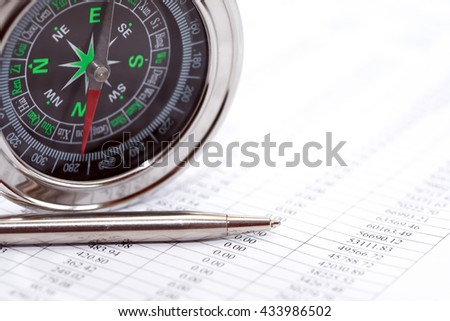 Business direction. Closeup of compass near pen on paper with digits - stock photo