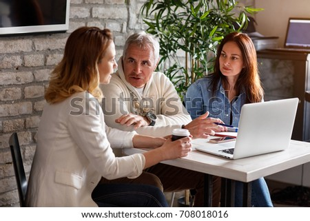 Business discussion at working table between male and female employees in office