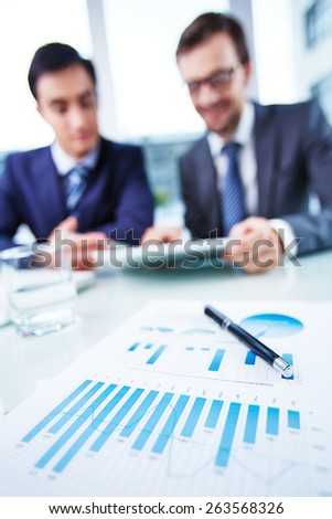 Business document at workplace and two businessmen working with touchpad on background - stock photo