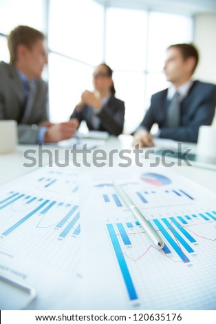 Business document on background of employees interacting at meeting - stock photo