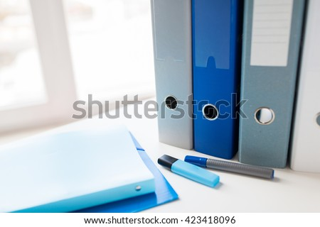 business, document, paperwork, office supply and education concept - close up of ring binders and files with highlighter pen or marker on table - stock photo