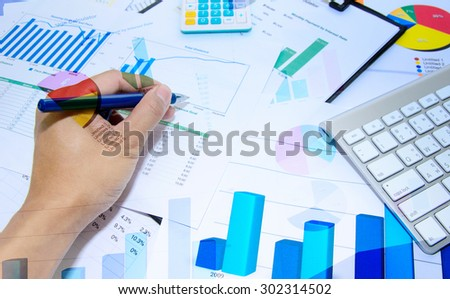 Business documents chart and pen on the table.