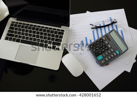 business documents on office table with laptop computer and graph business diagram and calculator in the background