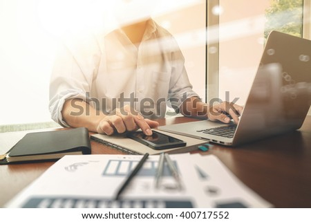business documents on office table with smart phone and digital laptop computer and graph business diagram and man working in the background