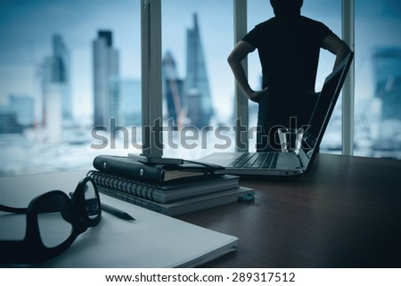 business documents on office table with smart phone and digital tablet and london city blurred view and man thinking in the background - stock photo