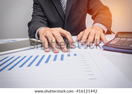 business documents on office table with smart phone and digital tablet and man working in the background.