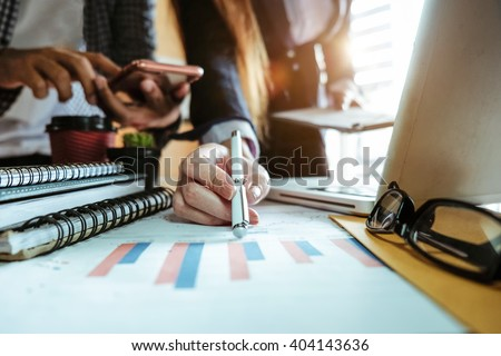 business documents on office table with smart phone and laptop and two colleagues discussing data in the background in morning light   - stock photo