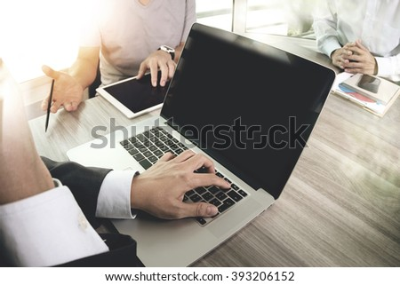 business documents on office table with smart phone and laptop computer and graph finance with social network diagram and three colleagues discussing data in the background
