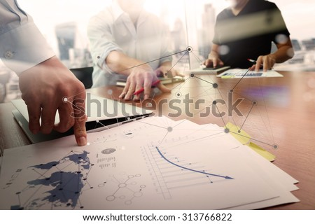 business documents on office table with smart phone and laptop computer and graph financial with social network diagram and two colleagues discussing data in the background - stock photo