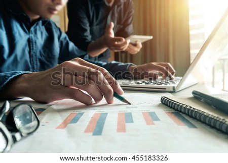 business documents on office table with tablet, smart phone and laptop and two colleagues discussing data in the background in morning light - stock photo