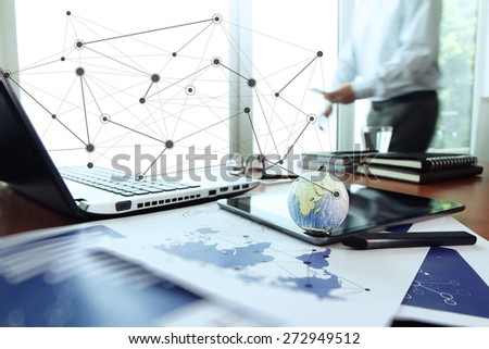 business documents on office table with texture the world on digital tablet and man using smart phone  in the background Elements of this image furnished by NASA - stock photo