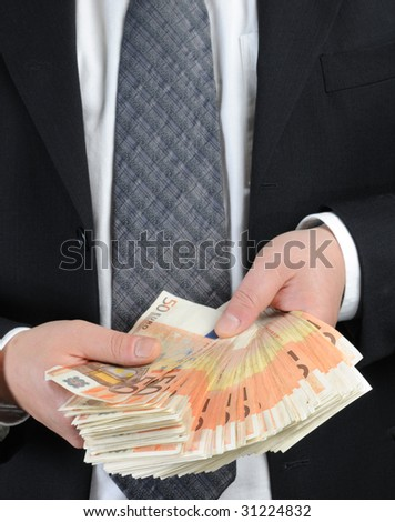 Business dressed man counts 50-euro banknotes - stock photo