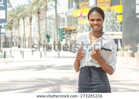Business Dubai. Smiling African businesswoman businessman holding tablet in hand in Dubai downtown among the skyscrapers showing thumb up and looking at the camera - stock photo
