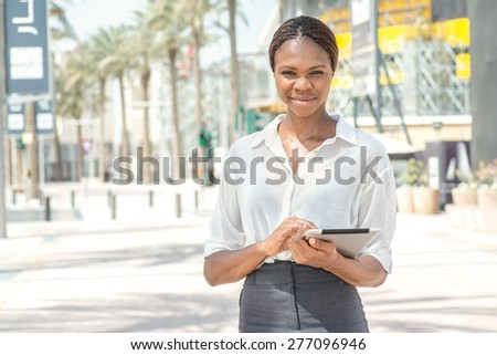 Business Dubai. Smiling African businesswoman businessman holding tablet in hand in Dubai downtown among the skyscrapers and looking at the camera