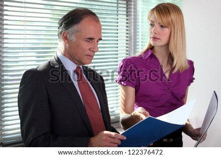 business duo consulting files in office - stock photo