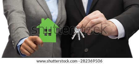 business, eco and real estate concept - businessman and businesswoman holding green house and keys - stock photo