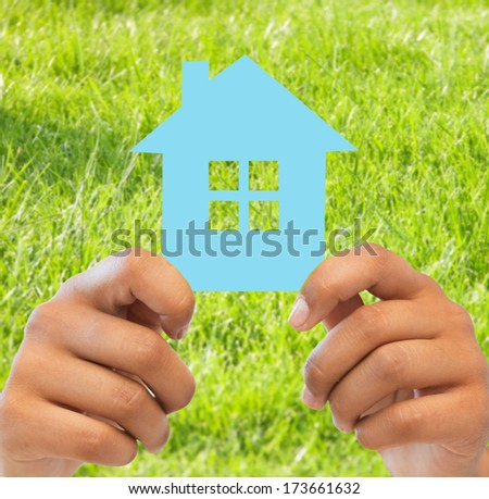 business, eco and real estate concept - closeup picture of woman hands holding blue house