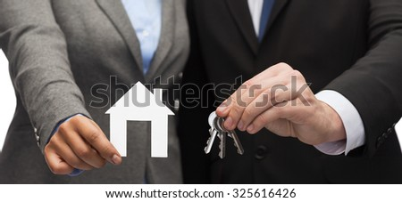 business, eco, real estate and office concept - businessman and businesswoman holding white paper house and keys - stock photo
