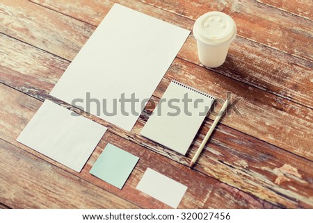 business, education and objects concept - close up of notebook, coffee cup , pencil and papers on table - stock photo