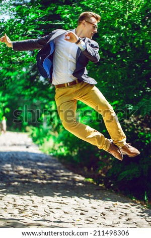 business, education and people concept - happy man  in trendy casual clothing and glasses, jumping on the nature background. Outdoor shoot. Copy-space - stock photo