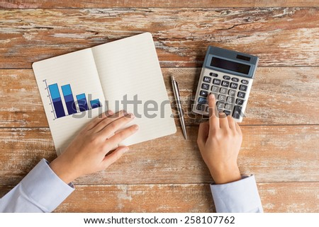 business, education, people and technology concept - close up of female hands with calculator, pen and chart drawing in notebook on table - stock photo