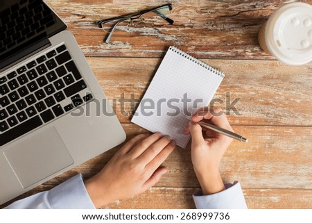 business, education, people and technology concept - close up of female hands with laptop computer, notebook and eyeglasses on table - stock photo