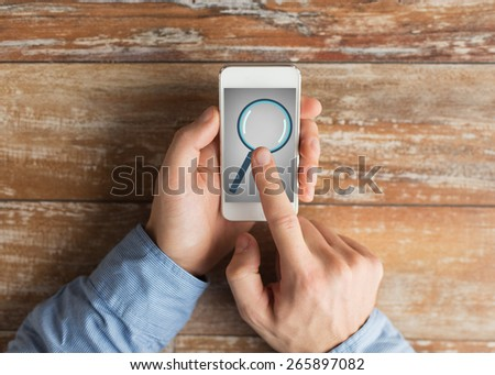 business, education, people and technology concept - close up of male hands holding smartphone with magnifying glass picture on screen at table - stock photo