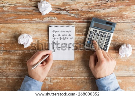 business, education, people and technology concept - close up of male hands with calculator, cramped paper wads and notebook solving mathematical task or equation - stock photo
