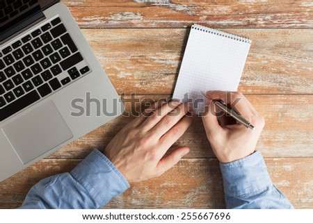 business, education, people and technology concept - close up of male hands with laptop computer, notebook and pen taking notes - stock photo