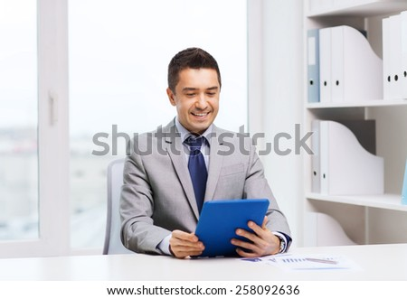 business, education, people and technology concept - smiling businessman with tablet pc computer in office - stock photo