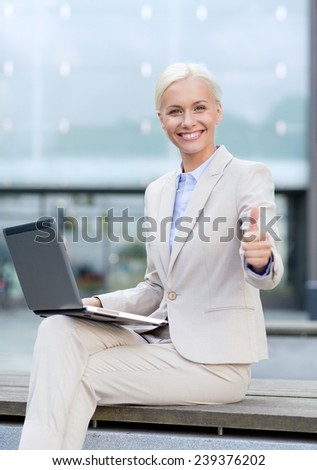 business, education, technology and people concept - smiling businesswoman working with laptop computer on city street - stock photo