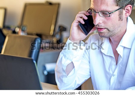 Business European Young Handsome Man,Shot Hair, wearing Eyeglasses,Talking and Holding Smart phone or Cell phone During Work on Laptop over Blurred Office with Morning Sun light, Business Concept. - stock photo