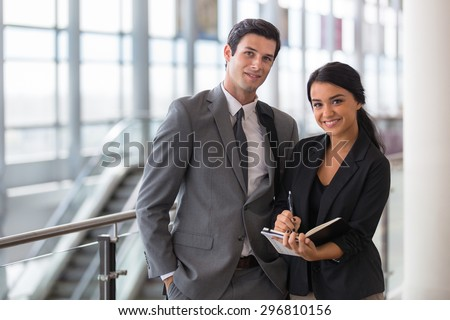 Business executive and assistant traveling at convention on a trip in the airport taking notes portrait