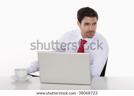 business executive in white shirt behind desk with laptop