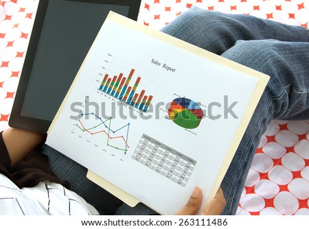 Business executive preparing presentation on corporate financial data and reports using  a tablet and wifi - stock photo
