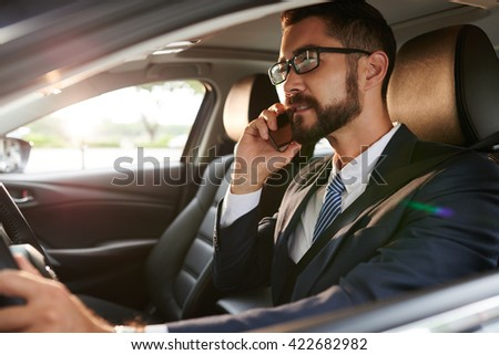 Business executive talking on phone when driving car