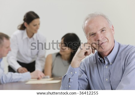 Business executive with head on hand pondering meeting - stock photo