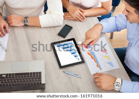 Business Executives At A Meeting Discussing Work On Digital Tablet - stock photo