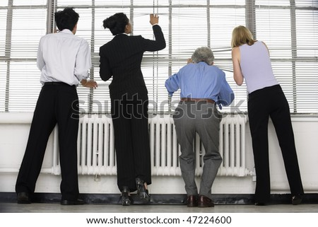 Business executives looking through blinds.