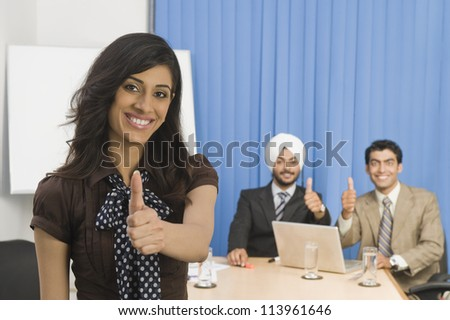 Business executives showing thumbs up and smiling - stock photo