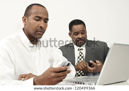 Business executives using cell phones at desk in office while working on laptop - stock photo