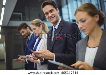 Business executives using electronic devices in corridor at office