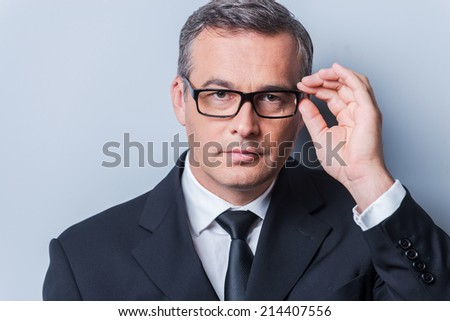 Business expert. Portrait of confident mature man in formalwear adjusting his eyeglasses and looking at camera  while standing against grey background - stock photo