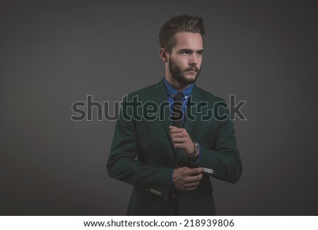 Business fashion man wearing green suit with blue shirt and black tie. Studio shot against grey.