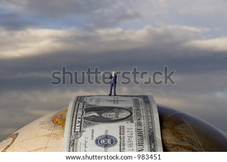 business figure standing on dollar bill, on a globe - stock photo