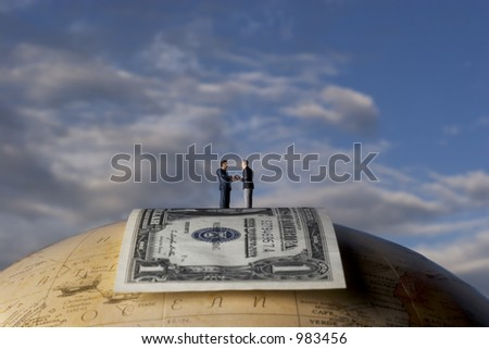 business figures standing on dollar bill, on a globe - stock photo